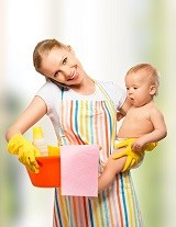 Happy mother cleaning with a baby in her hand